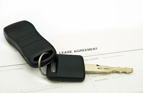set of car keys on top of lease agreement