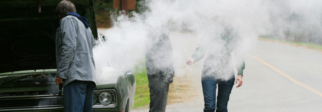 man checking under hood to figure out why his car is smoking two friends hidden by smoke