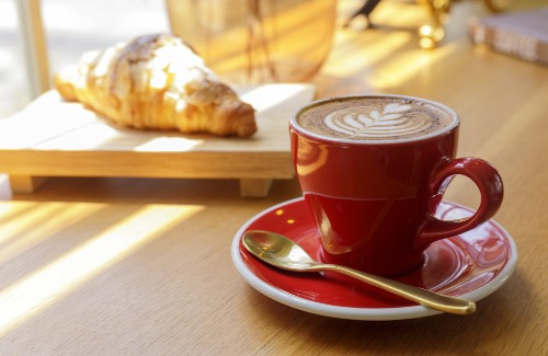 red cup of hot latte with scone on wooden board