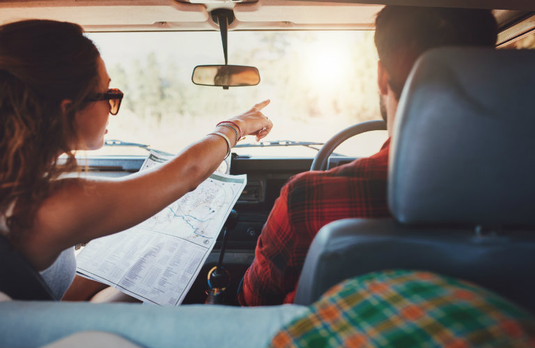 Man and women driving in a car with a map