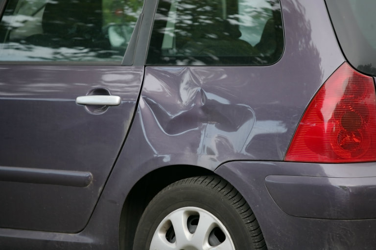 Dented side panel of a minivan