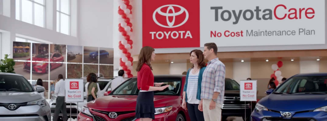 Three people in a Toyota showroom with a ToyotaCare sign hanging above them