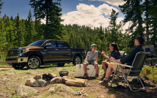 A family around an empty fire pit with the 2020 Toyota Tacoma in the background
