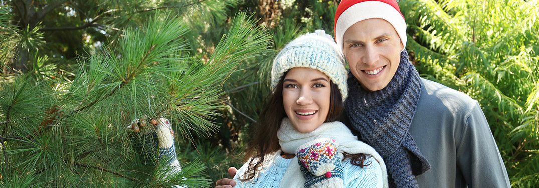 A man and a woman in front of a Christmas tree