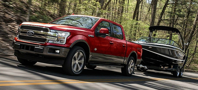 2018 Ford F-150 red side view towing a large black boat