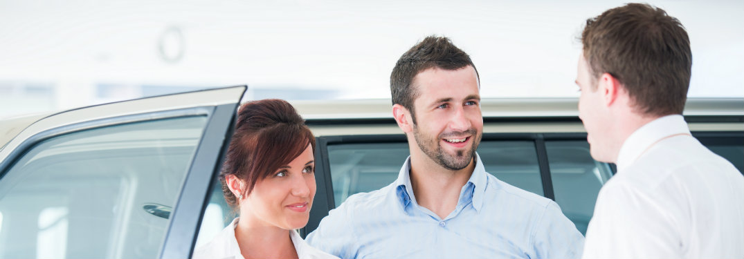 young couple looking at vehicles for sale on a car lot
