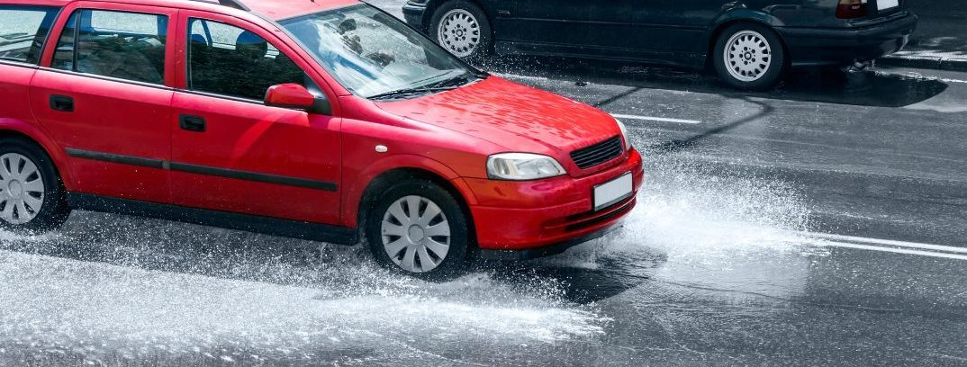 red car driving in rain on flooded street