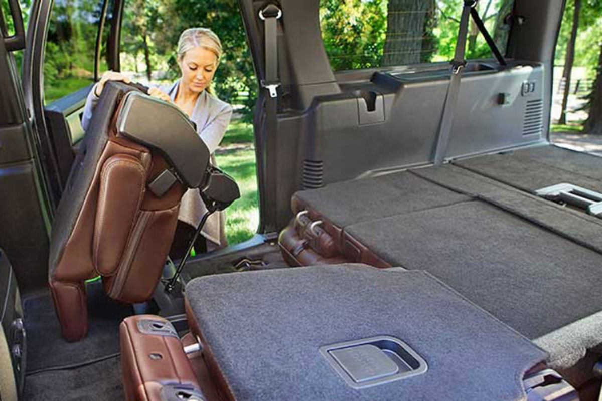 Woman folding the second-row seat of the 2017 Ford Expedition forward for easy access to the third-row seat