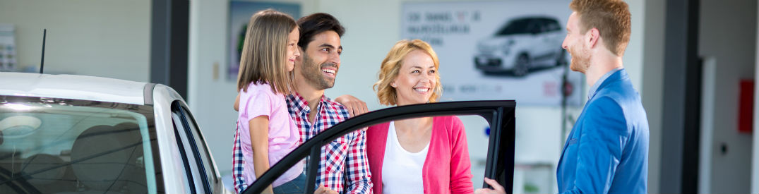 Salesperson helping happy family find a new car