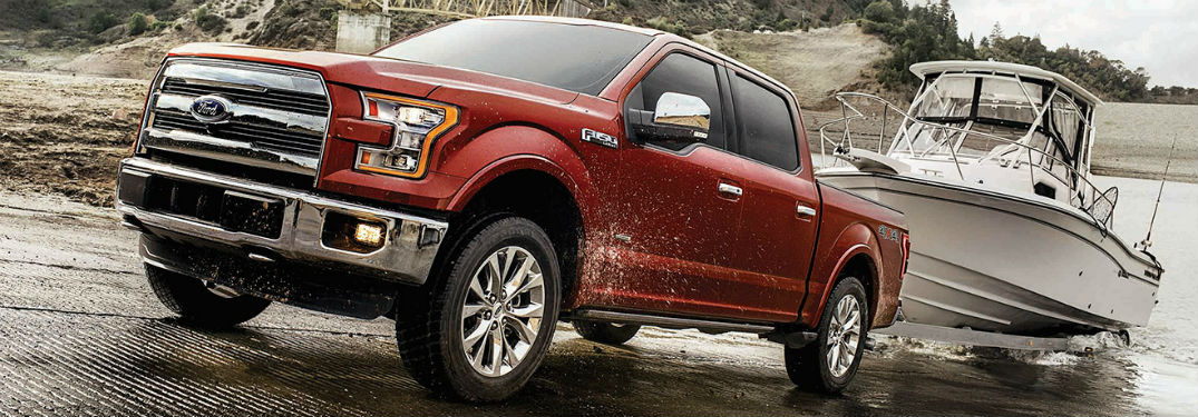 Front driver side exterior view of a red 2017 Ford F-150 pulling a boat