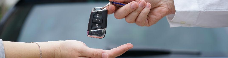 Salesman giving car keys to a customer