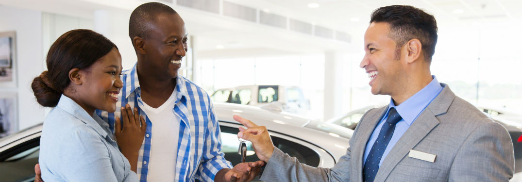 Smiling and happy couple receiving keys from a car salesman