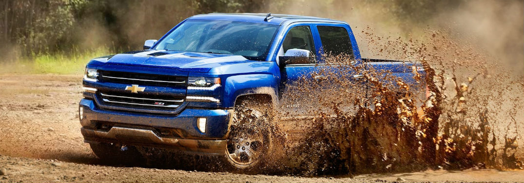 Front driver side exterior view of a blue 2018 Chevy Silverado 1500 driving through and ripping up mud