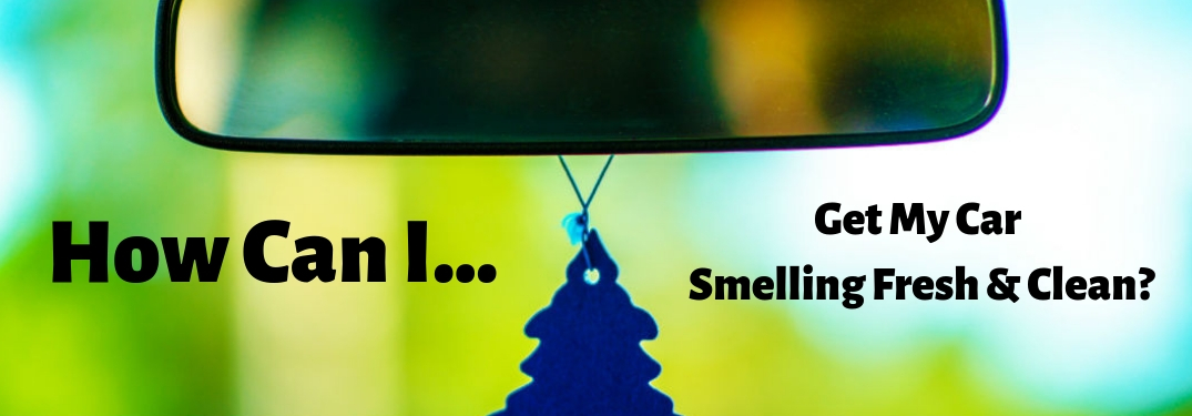 How Can I Get My Car Smelling Fresh & Clean, text on an image of a rearview mirror of a car with a blue Christmas tree air freshener hanging from it