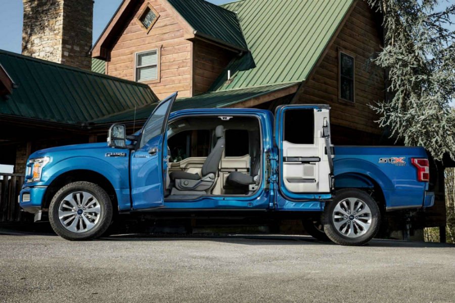 Driver side exterior view of a blue 2018 Ford F-150 with both driver side doors open