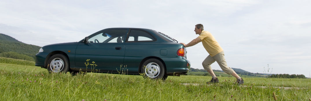 man pushing a car on the side of the road