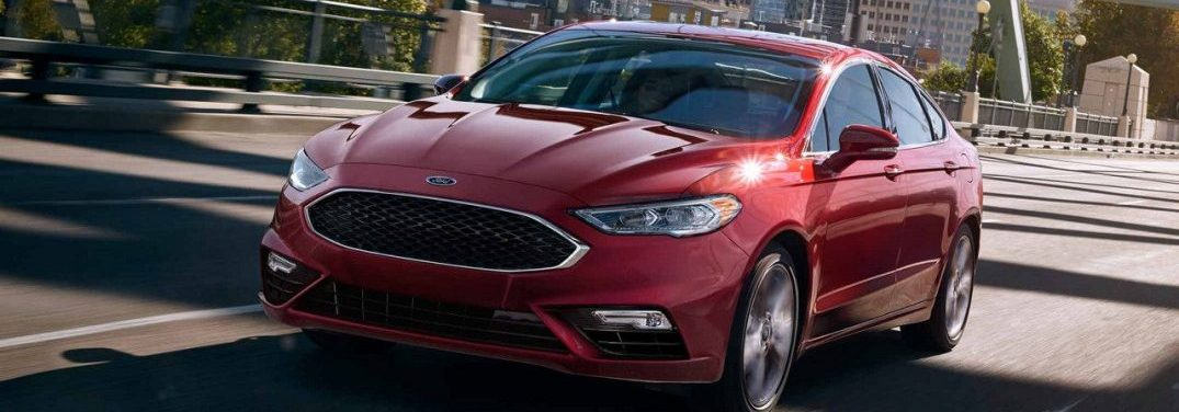 Red 2018 Ford Fusion driving on a city street
