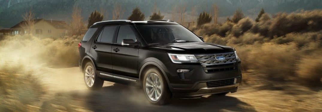 2018 Ford Explorer driving away from a house kicking up dust in a brush filled terrain