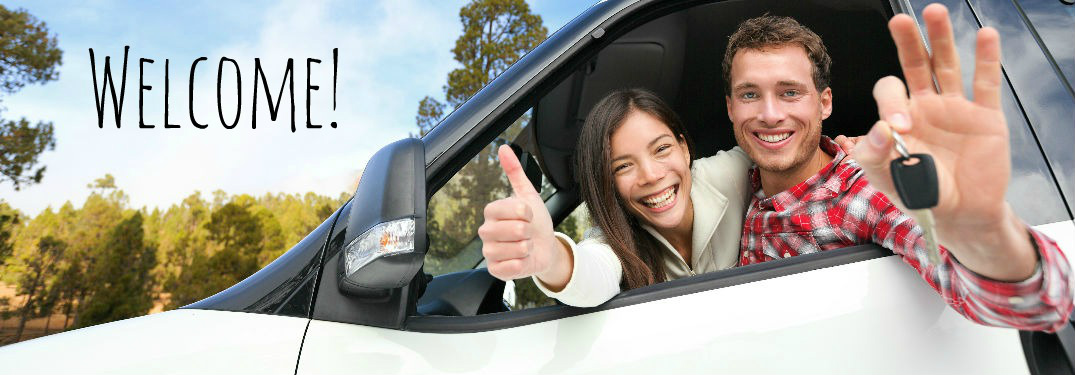 happy young couple in a car with woman giving thumbs up