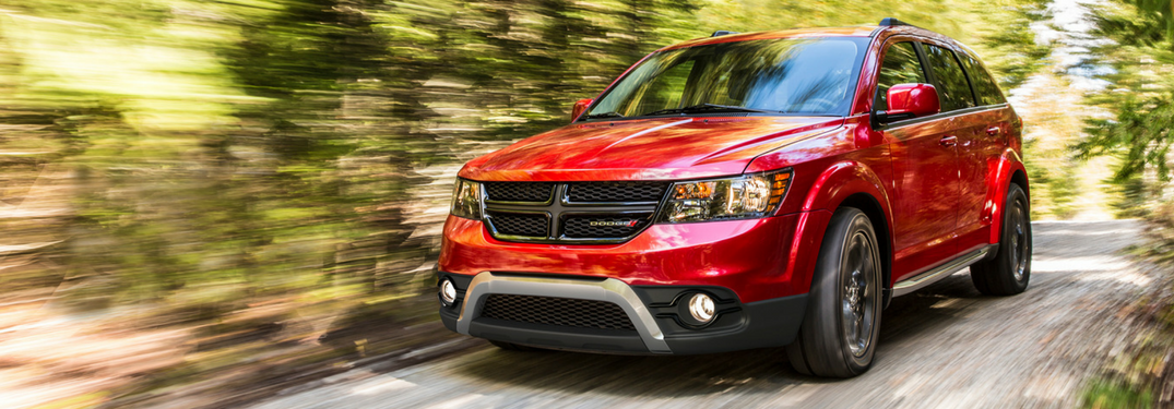 2018 Dodge Journey in red driving down wooded street