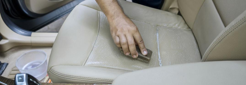 man scrubs down leather seat