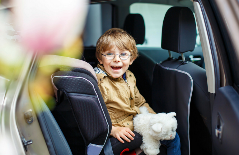 Little boy smiles from back of vehicle