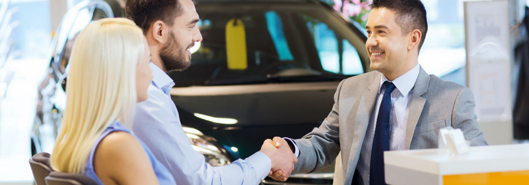 Pros and Cons of Buying a New Car with an image of a couple buying a new car from a salesman
