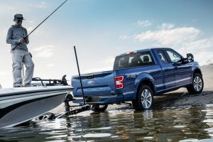 2019 Ford F-150 lowering a fishing boat into water with a fisher on it