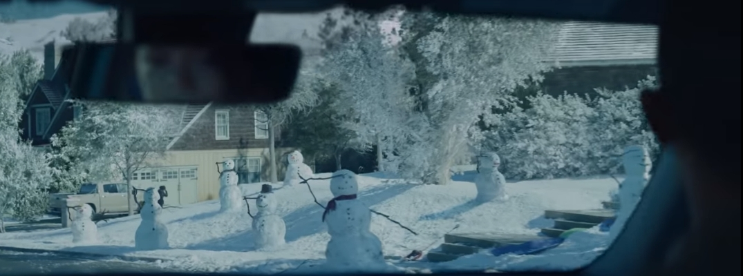 Line of snowmen saluting soldier in car