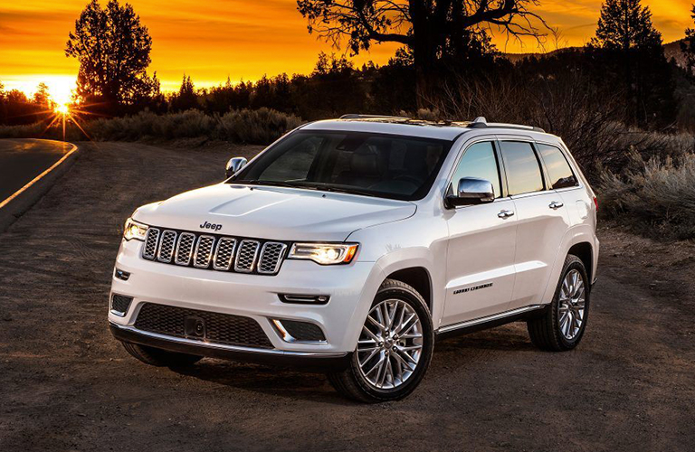 white 2019 Jeep Grand Cherokee in front of sunset