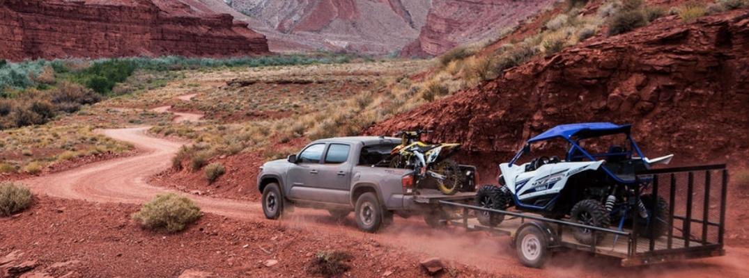 Grey 2019 Toyota Tacoma hauling four-wheeler on trailer bed