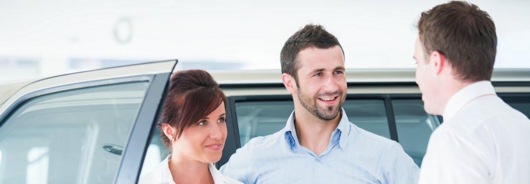 couple standing by car talking to salesman