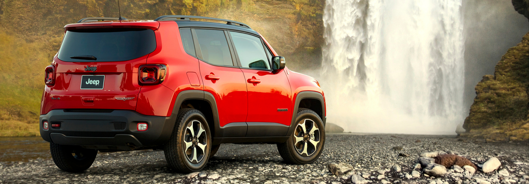 Red 2020 Jeep Renegade in front of waterfall from rear passenger view