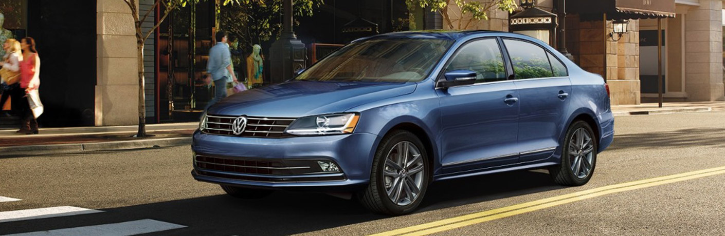 Blue 2018 Volkswagen Jetta parked on the side of the road in front of some trees.