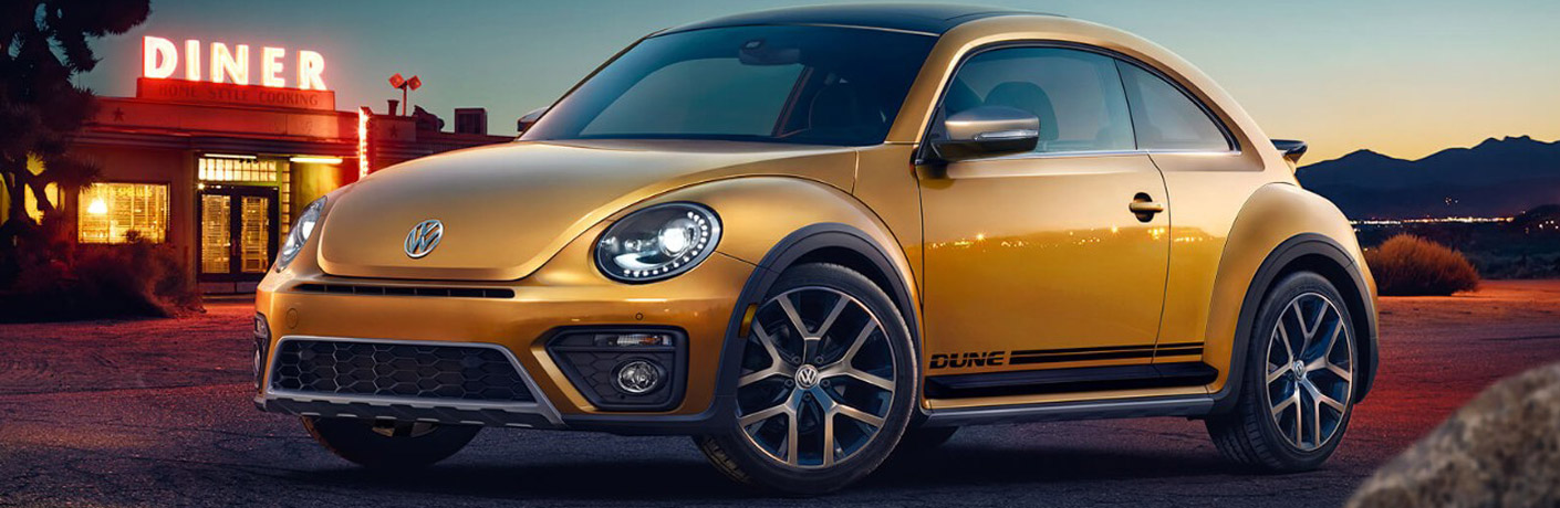 Gold Volkswagen Beetle parked in front of a gas staton