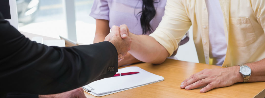A stock photo of two people shaking hands after completing a deal