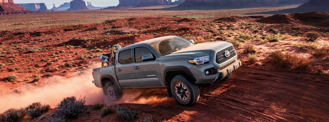 A 2018 Toyota Tacoma driving through the desert heading from left to right over a berm.