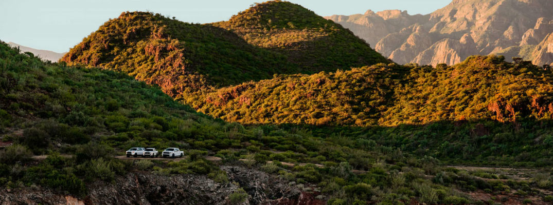 A long range photo showing three Toyota vehicles parked near mountains
