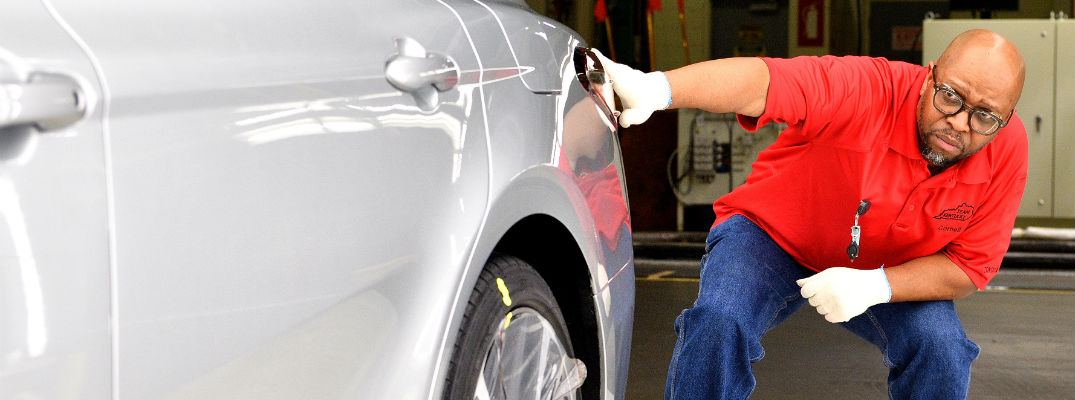 A photo of a Toyota official closely examining a car