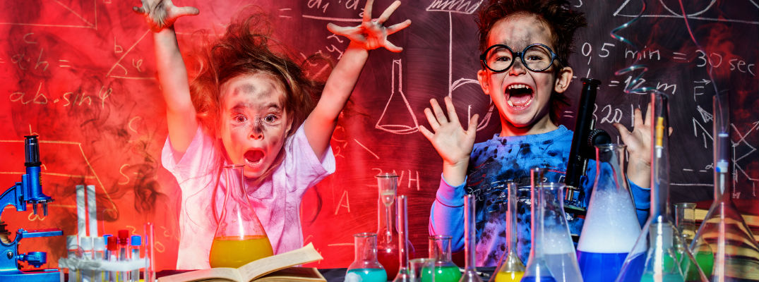 A stock photo of two children making a mess with science.