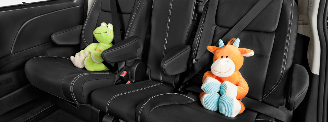 A photo of two stuffed animals buckled into the rear seats of a Toyota Sienna