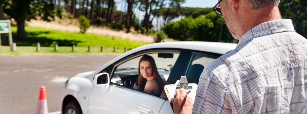 A stock photo of young woman taking a driving test with an instructor holding a clipboard.