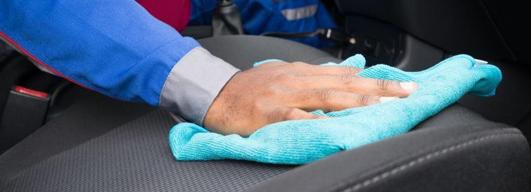 man wiping down interior of car with blue cloth