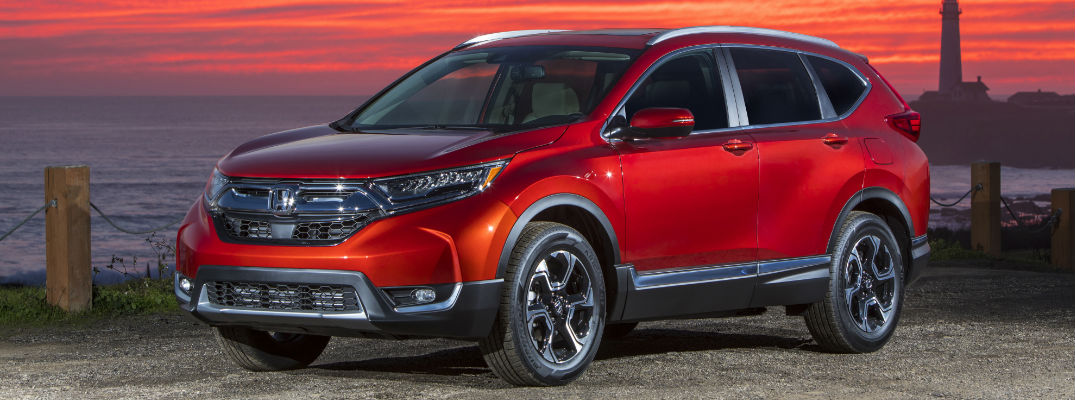 2018 Honda CR-V Side View of Red Exterior with sunset behind it