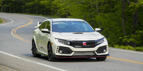 Front wiew of 2018 Honda Civic Type R in Championship White driving on road in woods