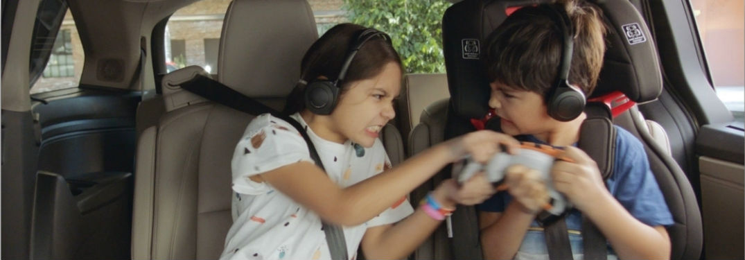 Two children fighting over a toy in the backseat of the Odyssey