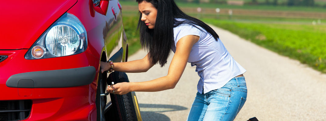A stock photo of a person putting a donut spare tire on their vehicle.