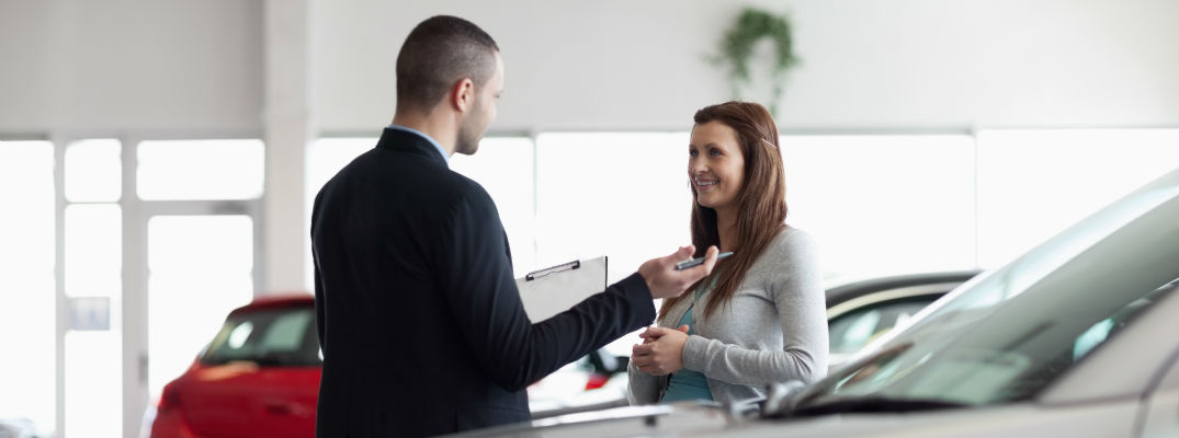 A stock photo of a product expert helping a client buy a vehicle.
