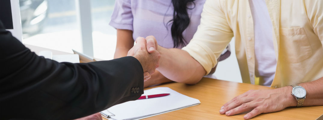A stock photo of people shaking hands after filling out paperwork.