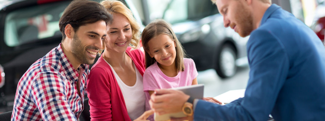 A stock photo of a family learning more about a new vehicle they may buy.